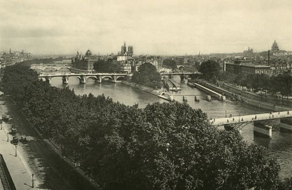 General view of the centre of Paris. That's Notre-Dame on the skyline, and over to the right you can see Le Pantheon. The pedestrian bridge nearest us is the Pont des Arts. Date: circa 1900