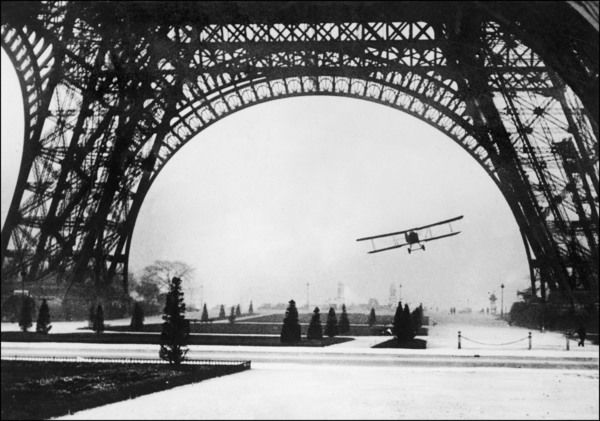 French aviator Lieutenant Collot successfully flies his biplane beneath the Tour Eiffel, but in a moment he will hit a cable and crash fatally