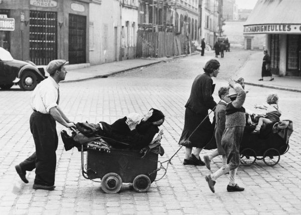 Parisians leaving the city for safer havens. Here a poor family is using all possible means of locomotion to leave, wheeling their grandmother in a pram