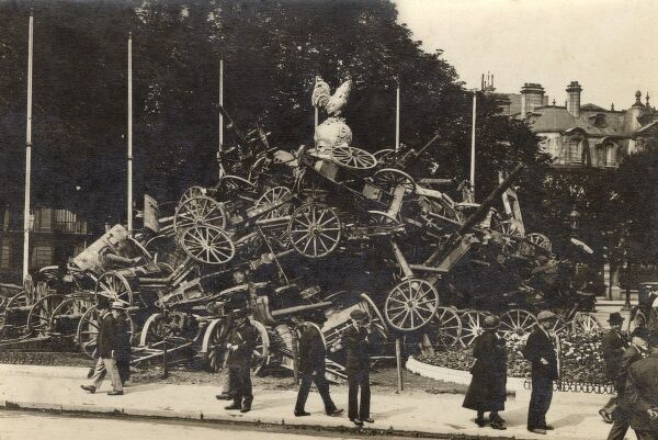 A mound of artillery pieces in a very symbolic gesture of abandonment of the war effort at the final closure of World War One in 1918. The whole mass of wheels and guns is topped with a gilt French cockerel and an orb, inscribed with '1918&#39
