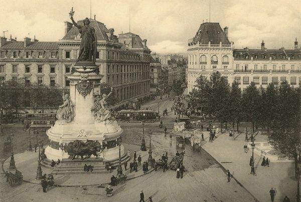 Trams pass along one side of this square where flower- sellers ply their trade. Date: circa 1904