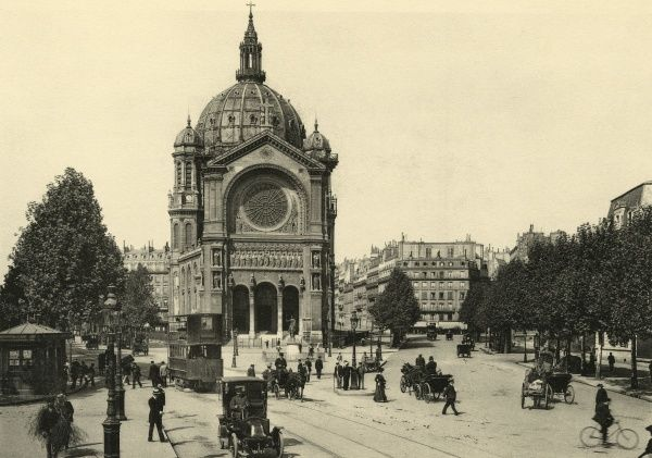 Cars, bicycles and a tram pass the curious architecture of Saint-Augustin. Date: circa 1904