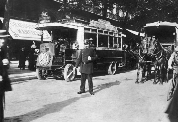 Traffic in a Paris street, a policeman controls both motor buses and horse carriages