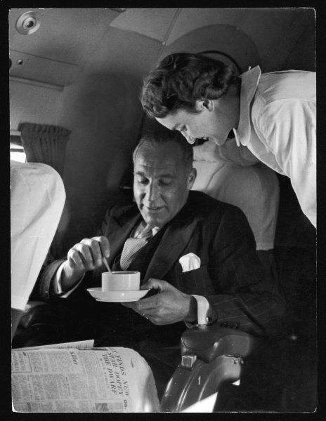 An attentive 'Swissair' air hostess serves a smart gentleman a cup of coffee