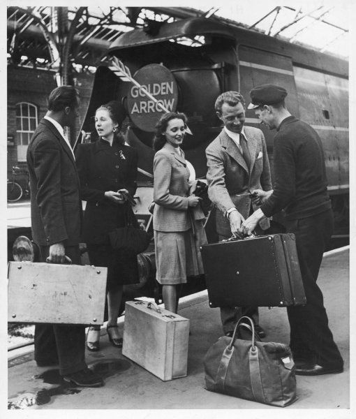 A group of rail passengers stand on a platform with their luggage before boarding the 'Golden Arrow' luxury train from London-Dover-Calais