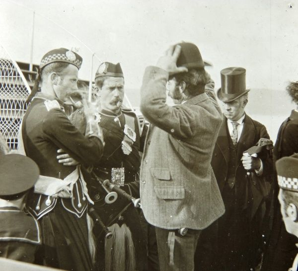 A group of passengers waiting to board a boat. There are two Scottish pipers in traditional costume on the left, a man in a bowler hat in the middle, and a man in a top hat on the right