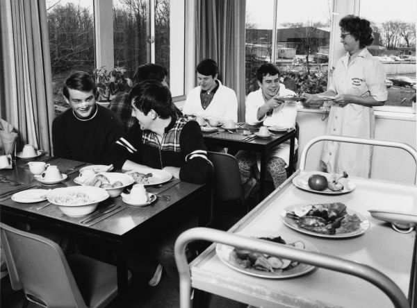 Scene at the Metropolitan Police Medical Centre, Hendon, north west London, showing five patients in the cafeteria enjoying a hot meal served by a catering lady. Three patients are in dressing gown and pyjamas, two are in daytime clothing