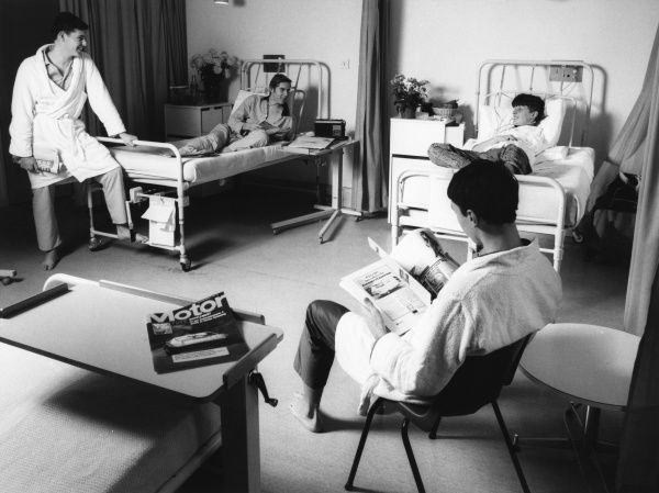 Scene at the Metropolitan Police Medical Centre, Hendon, north west London, showing four patients in dressing gowns and pyjamas chatting in a hospital ward