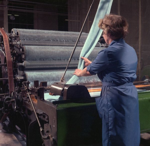 A woman factory worker in blue uniform feeds light blue thread into a large piece of (possibly weaving?) machinery at Patons & Baldwins factory in Darlington