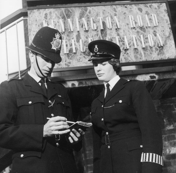 A PC and a WPC outside Kennington Road police station in south east London. The policeman is checking his notebook while the policewoman watches