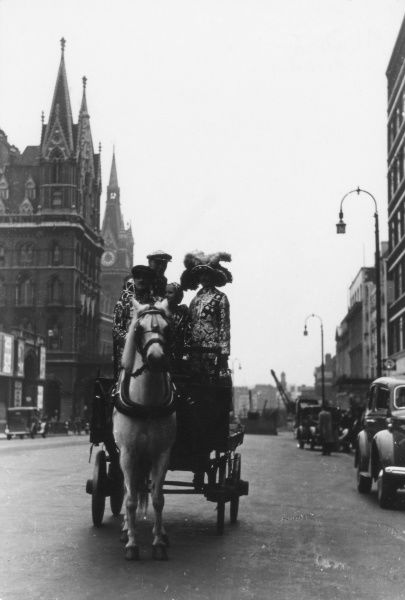 Pearly Kings and Queens riding their horse and carriage past King's Cross St. Pancras stations, London. Date: 1930s