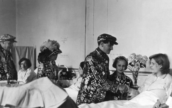 London Pearly Kings and Queens visiting young women in their hospital beds. Date: 1930s