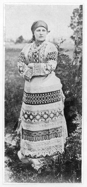 A Russian peasant girl in a highly decorative full-length dress