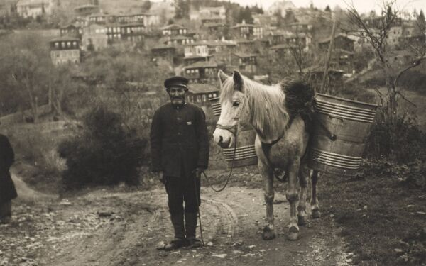 A peasant working man in Istanbul on the Asian side of the Bosphorus stands with his white horse carrying two large metal containers on either flank