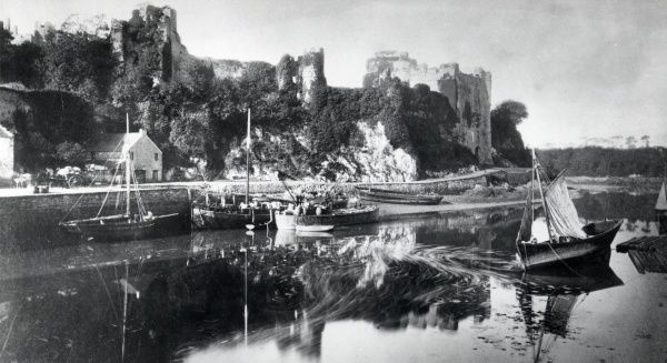 View of the ivy-covered ruins of Pembroke Castle, viewed from across the water, in Pembrokeshire, West Wales. The castle dates from the 11th century. Extensive restoration work has been carried out since this photograph was taken