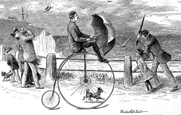 Engraving showing a cyclist riding a 'Penny Farthing' bicycle using an umbrella to 'sail' along on a windy day at the British seaside