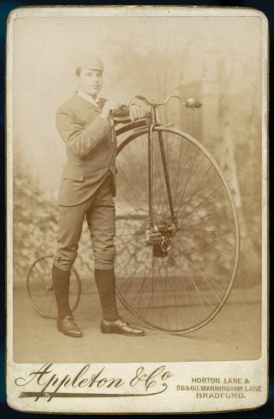 A young man and his 'Ordinary' bicycle, known as a 'penny farthing, pose proudly for a studio camera