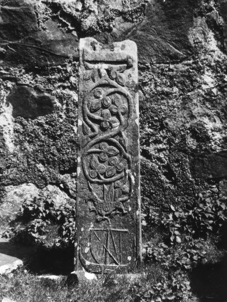 The Celtic Cross at Pennygown, Isle of Mull, Argyllshire, Scotland. One one side is a circular design, ending in the tail of a crouching griffin, with a galley underneath it. Date: 1930s