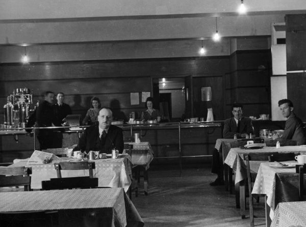 People in a cafe, sitting at tables and serving behind the counter. The lighting comes from bare, unshaded lightbulbs.  circa 1940s