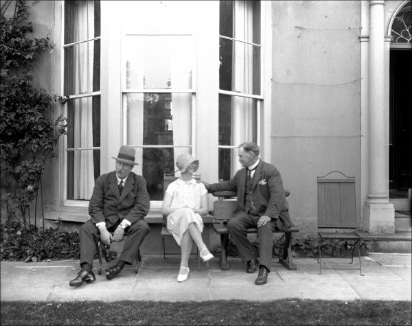 A woman and two men sitting on the rear terrace of a large house in Devon
