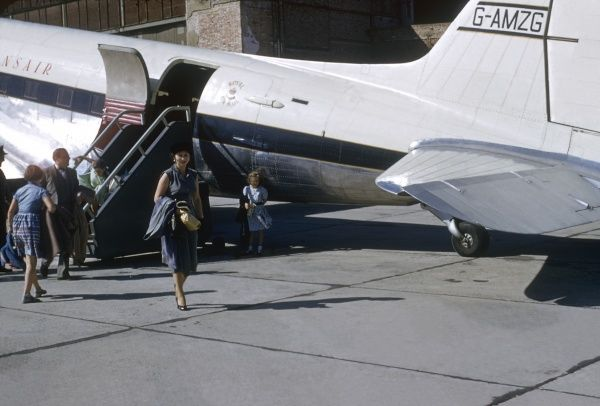 A group of people disembarking from an aeroplane operated by Transair, in Vienna, Austria. (2 of 3)