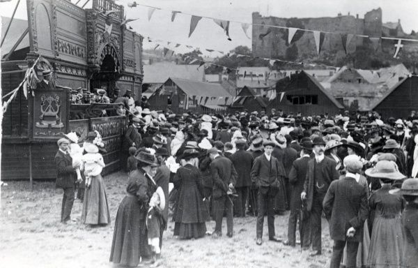Crowds of people milling around at the fair, on land adjacent to the New Bridge in Haverfordwest, Pembrokeshire, Dyfed, South Wales