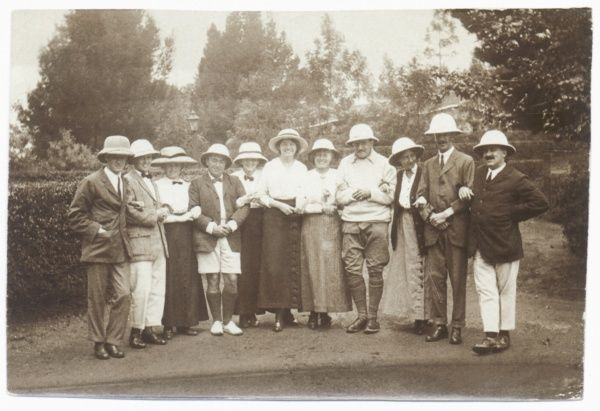 Eleven people in a garden wearing pith helmets -- six men and five women. One of the men is wearing shorts, and another man is in jodhpurs; the women are wearing ankle-length skirts. They are all standing in one row with their arms linked
