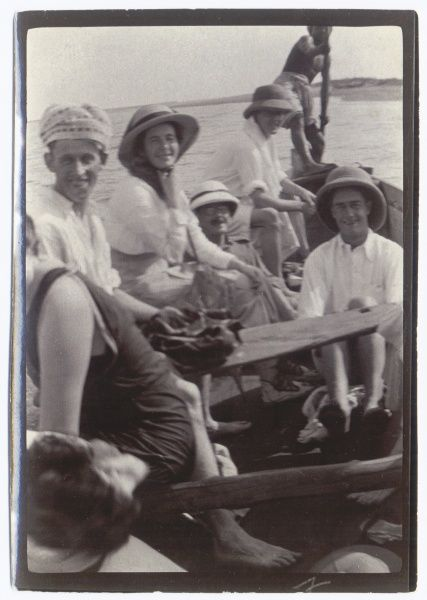 A group of people enjoying an outing in a punt, somewhere in the Middle East. Most of them are wearing pith helmets. At the far end of the boat is a native man using a punting pole