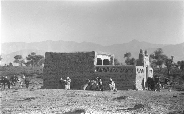 An unidentified location, somewhere in the Middle East: a small square building like a fort, with a few people and animals outside. There are hills or mountains in the background