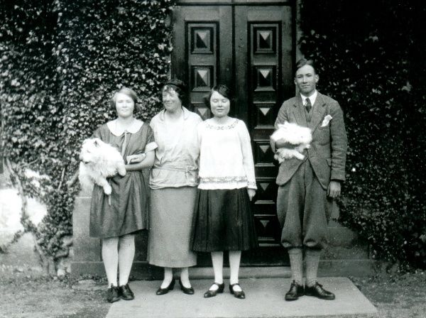 Four people pose outside a front door with two pet dogs, somewhere in Scotland. The young man on the right is wearing plus fours