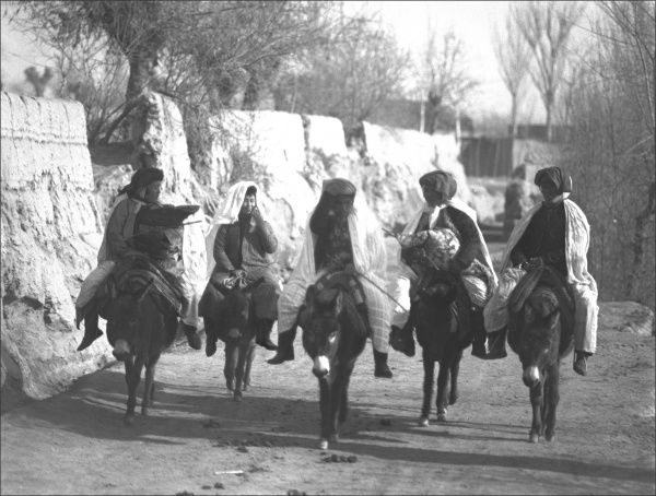 Five people on a road in Kashgar, western China, riding donkeys