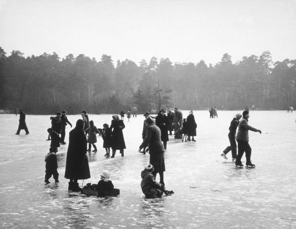 Locals make the best of the winter weather by skating on Wisley Pond whilst it is frozen over, Surrey, England