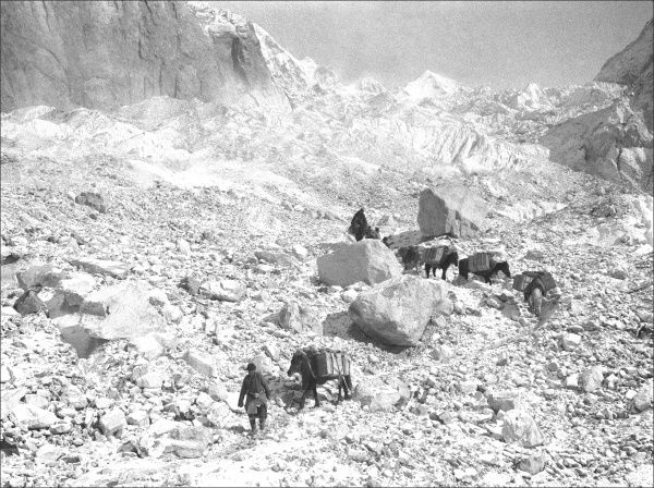 People travelling through rocky terrain in Kashgar, western China. Date: 1932