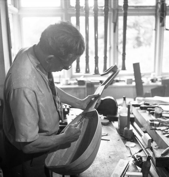 A company specialising in the production of period musical instruments. A man tightens the screws which hold the neck of a lute to the body
