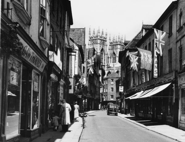 A view of Petergate, York, during festival time, with the towers of the Minster in the background