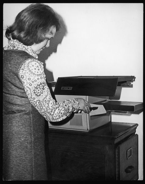 "A woman in a floral shirt, denim dress and with a ""page boy"" hairstyle, using an early form of photocopier"