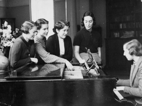 Four young ladies listening to a piano recital. Date: 1930s
