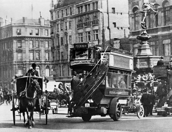 A horse cab passes a motor bus by the statue of Eros in Piccadilly Circus, London