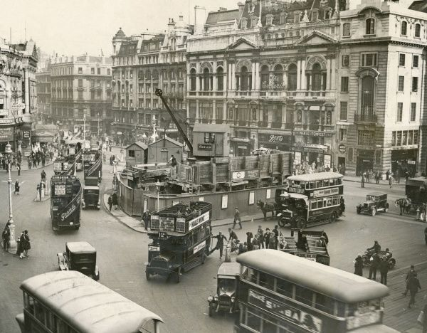 More changes to the traffic layout at Piccadilly Circus - work in progress round the Eros statue, which I suppose is somewhere behind the hoardings. Date: 1928