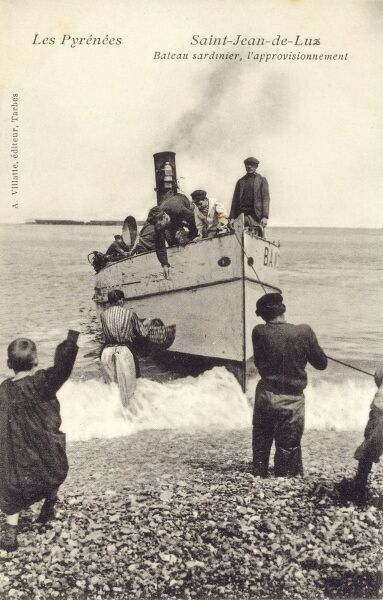 A small steam-powered sardine fishing boat picks up provisions for the fishermen crew from a beach at Saint-Jean-de-Luz, South west France. Date: 1906