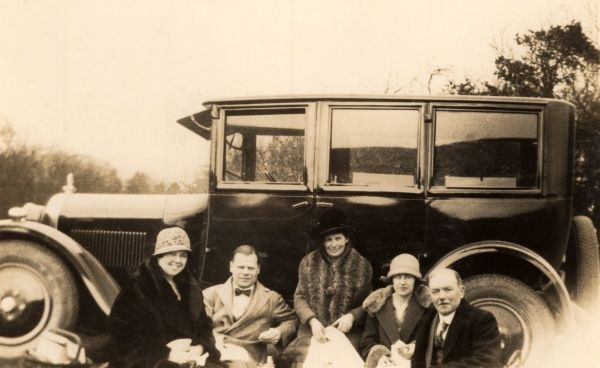 A group of men and women having a picnic in the shade of a large family saloon car
