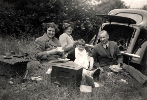 Enjoying a picnic out of the boot of a Morris 8 E series 4 door Six Light