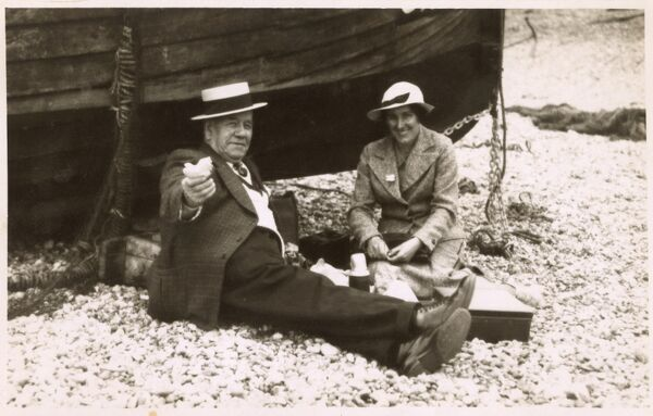 A couple have a picnic by the seaside, using a fishing boat as a shelter from the stiff breeze (possibly!)... Date: circa 1940s