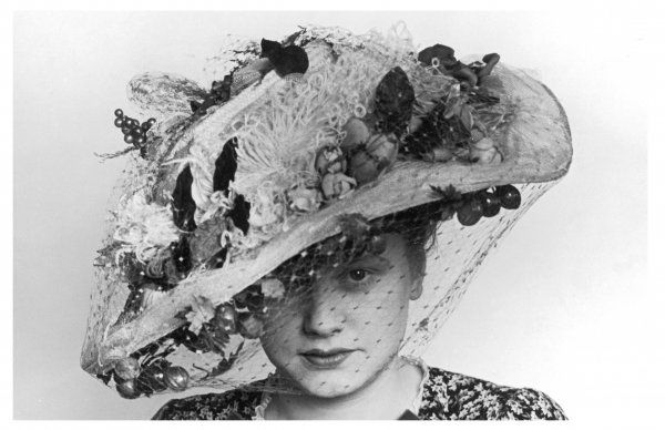 Ascot hat: broad brimmed straw picture hat laden with a profusion of fruit, flowers & feathers including roses, grapes & ostrich plumes & secured with a net veil