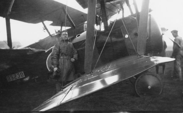 A pilot standing in front of his biplane on an airfield during the First World War. Date: 1914-1918