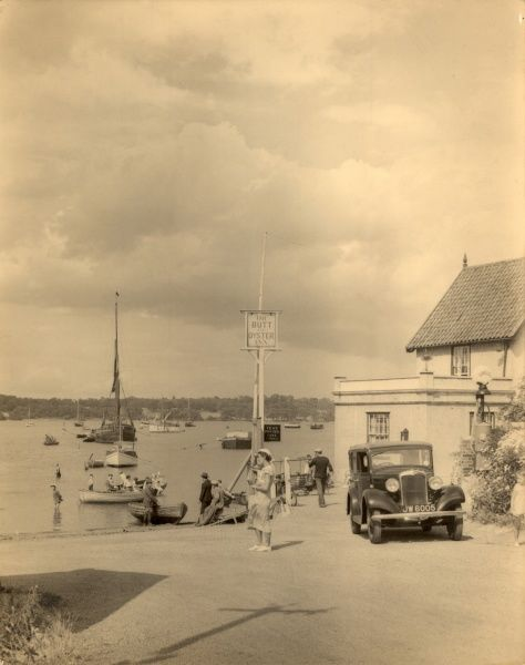 A charmingly nostalgic scene from around 1932 showing Pin Mill near Ipswich in Suffolk, with a vintage car in the foreground, and numerous boats sailing around on the water beyond