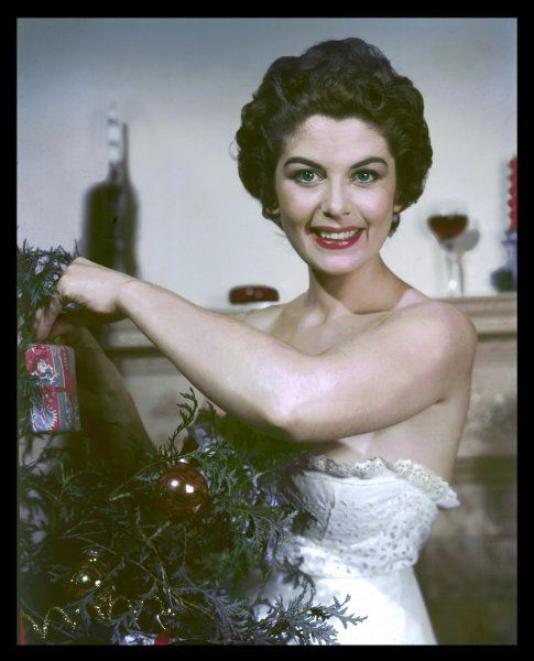 A grinning brunette model, wearing a strapless broderie anglaise top, busily decks her Christmas tree ready for the big day