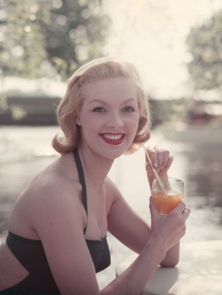 A pretty blonde model in a halter-neck one-piece bathing costume with cut-out back relaxes while enjoying a fruit juice. The straw will ensure her lipstick won't smudge