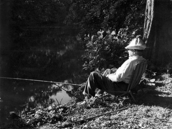 'Piscatorial Relaxation' : An old angler enjoying a spot of fly fishing on the banks of a lake in Essex, England. Date: 1950s