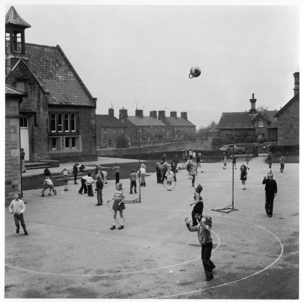 A pupil of Pilsey Village School throws a ball high up in the air in the school playground